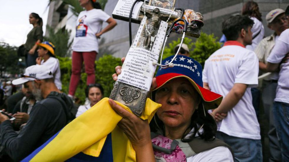 Opposition supporters demonstrate outside the headquarters of the United Nations Development Programme during the visit of the UN High Commissioner for Human Rights Michelle Bachelet, in Caracas on June 21, 2019. - Bachelet arrived in Venezuela Wednesday as part of a visit to review the country's ongoing economic and political crisis. (Photo by CRISTIAN HERNANDEZ / AFP)