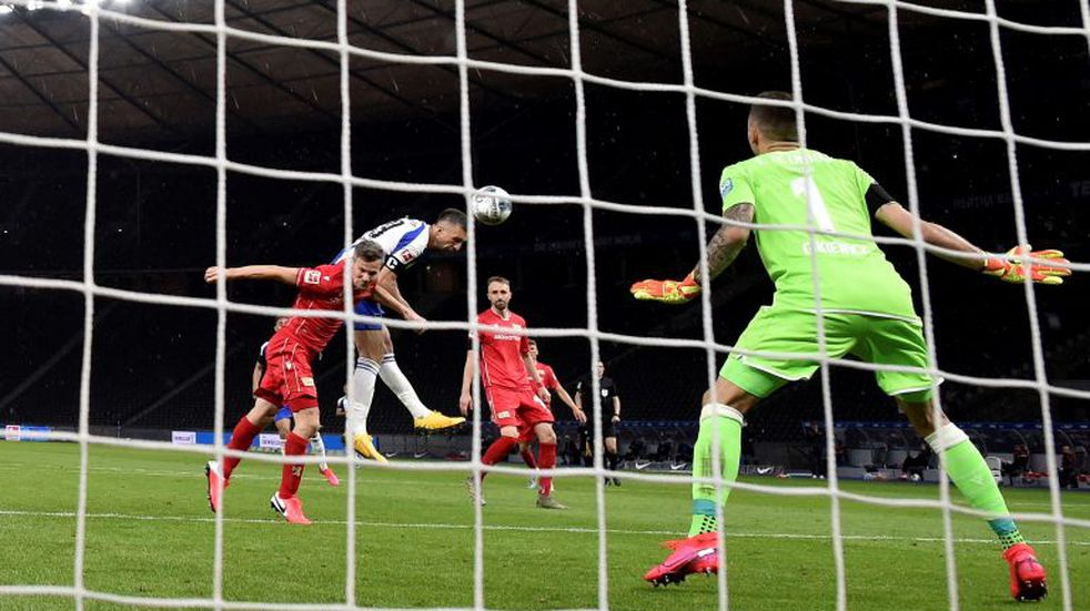 Hertha' s Vedad Ibisevic, second left, scores the opening goal during the German Bundesliga soccer match between Hertha BSC Berlin and 1. FC Union Berlin in Berlin, Germany, Friday, May 22, 2020. The German Bundesliga is the world's first major soccer league to resume after a two-month suspension because of the coronavirus pandemic. (Stuart Franklin/Pool Photo via AP)