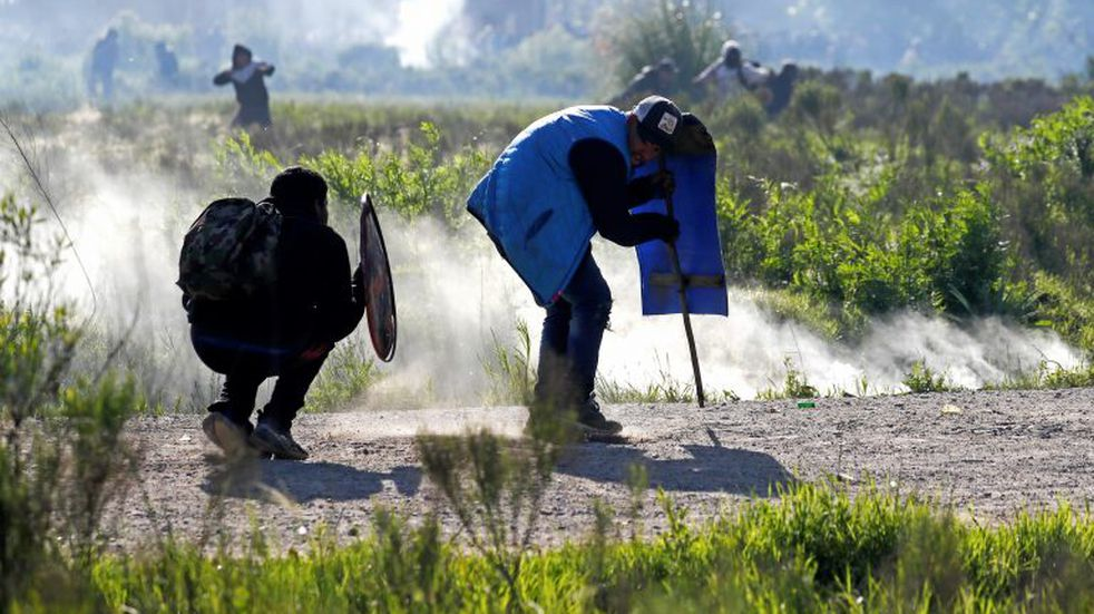 Squatters clash with police evicting them from a field where they lived in Guernica, Buenos Aires province, Argentina, Thursday, Oct. 29, 2020. A court ordered the eviction of families who are squatting here since July, but the families say they have nowhere to go amid the COVID-19 pandemic. (AP Photo/Natacha Pisarenko)