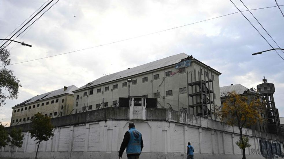 Police officers walk outside Villa Devoto prison as inmates appear from a hole on the destroyed roof of the prison during a riot in demand of preventive measures against the spread of COVID-19 after a case of the novel coronavirus was confirmed inside the facility, in Buenos Aires on April 24, 2020. (Photo by Juan MABROMATA / AFP)