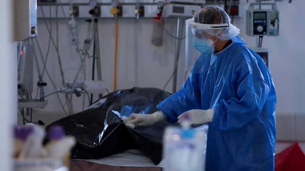 A health worker cleans the bodybag of a COVID-19 victim in the intensive care unit (ICU) of a hospital in Buenos Aires, Argentina, Tuesday, Aug. 18, 2020. (AP Photo/Natacha Pisarenko)   muerto coronavirus casos del dia