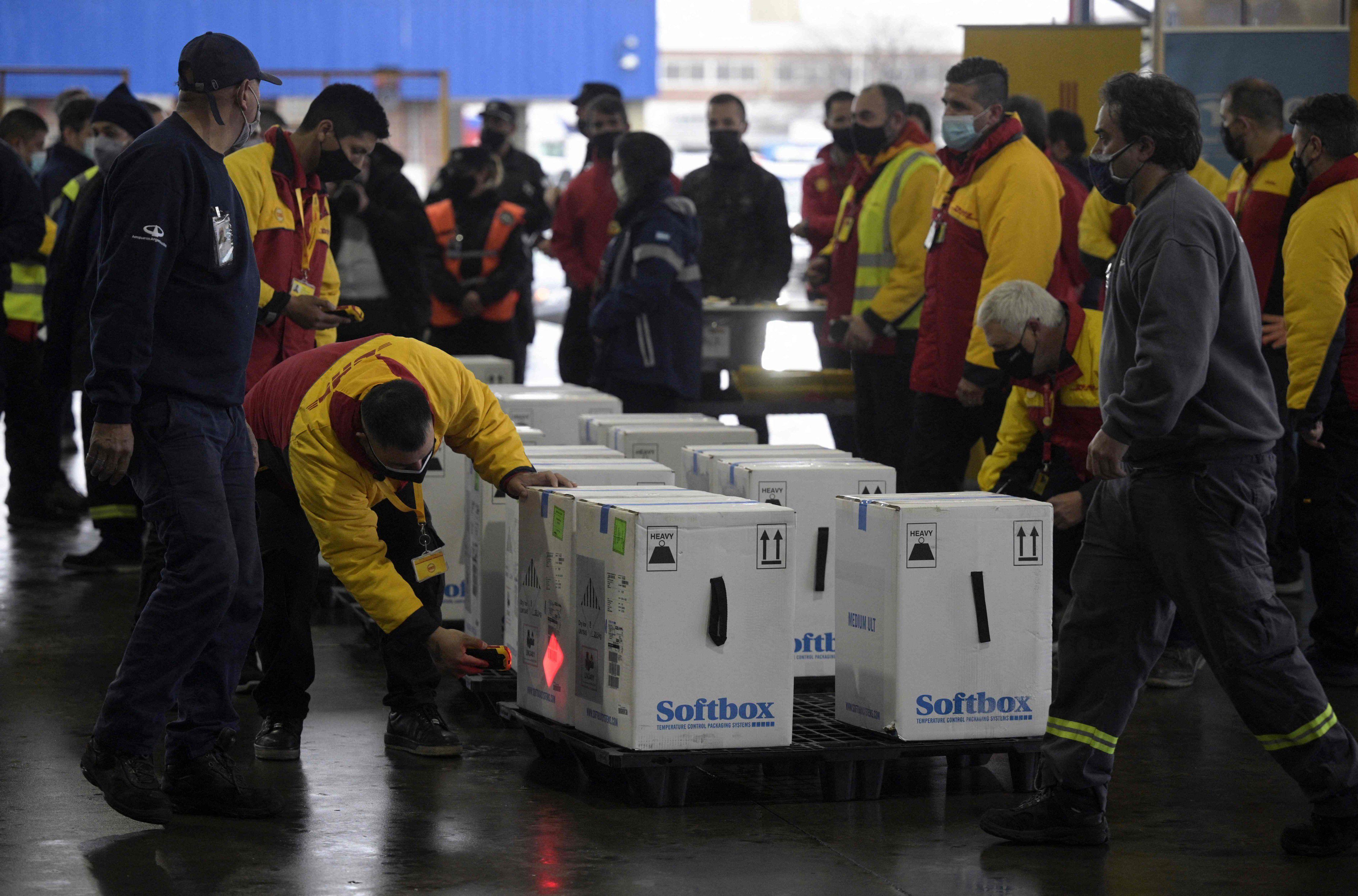 Trabajadores en Ezeiza descargan dosis de la vacuna Pfizer.