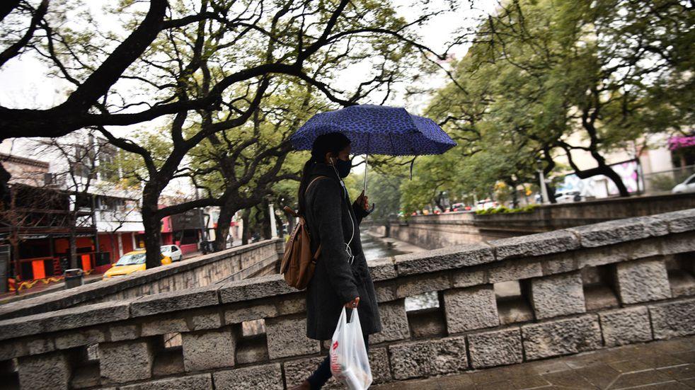 Llovizna en Córdoba. Una mujer con paraguas cruza La Cañada. (Pedro Castillo/ La Voz)