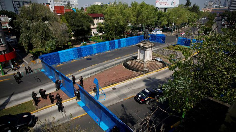 Police officers stand guard in front of metal fencing surrounding the statue of Italian explorer Cristobal Colon, also known as Christopher Columbus, during Columbus Day, or Day of the Race (Dia de la Raza), in remembrance of when Colon came to the Americas, in Mexico City, Mexico October 12, 2020, REUTERS/Gustavo Graf