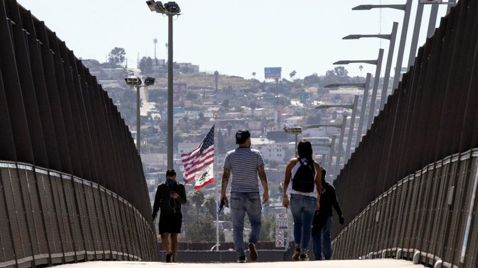 La Mesa (United States), 22/04/2020.- People wearing face masks cross the bridge over the 805 freeway at the US-Mexican border amid the coronavirus pandemic in the district of San Ysidro, San Diego, California, USA, 22 April 2020. US President Donald J. Trump stated he had signed an executive order temporarily stopping some green cards and work visas from being issued, in order to reportedly protect native born worker's employment opportunities during the coronavirus pandemic. (Estados Unidos) EFE/EPA/ETIENNE LAURENT